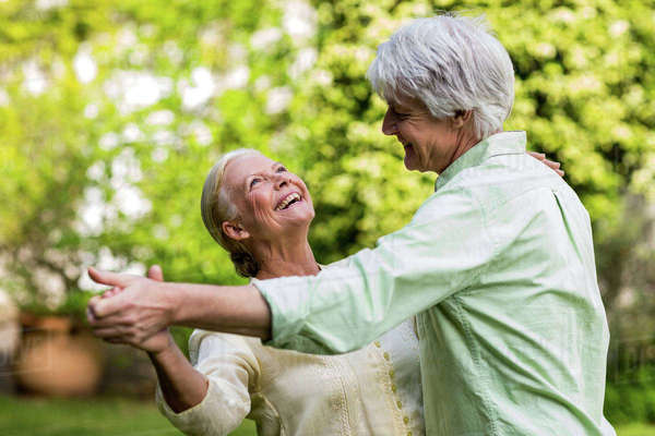 Happy smiling senior woman looking up while dancing with man in yard Royalty-free stock photo