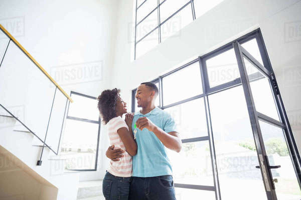 Happy couple embracing and showing house key in their new home Royalty-free stock photo