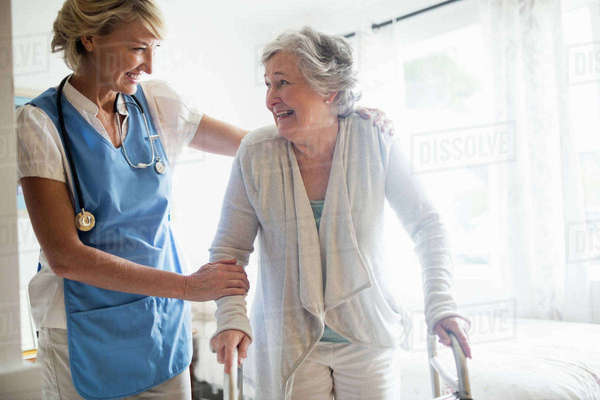 Nurse helping senior woman to stand up in a retirement home Royalty-free stock photo
