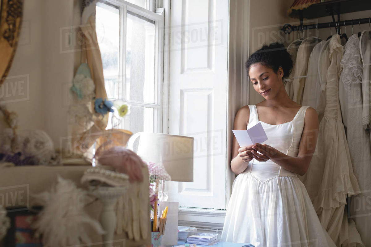 Young Bride In Wedding Dress Reading A Note At Boutique