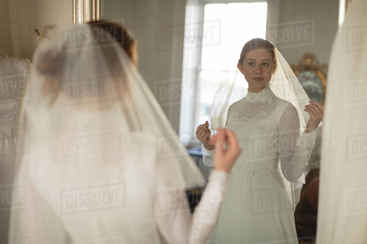 Young bride in a wedding dress looking at mirror in the boutique ...