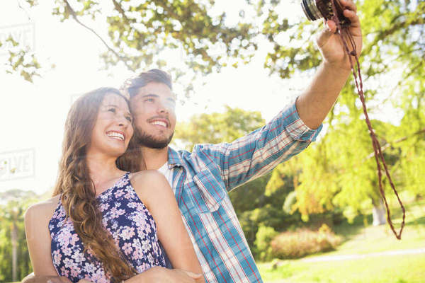 Cute couple doing selfie with retro camera in the park on a sunny day  Royalty-free stock photo