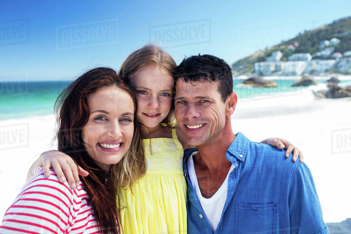 Cute family smiling with arms around on the beach royalty free stock photo