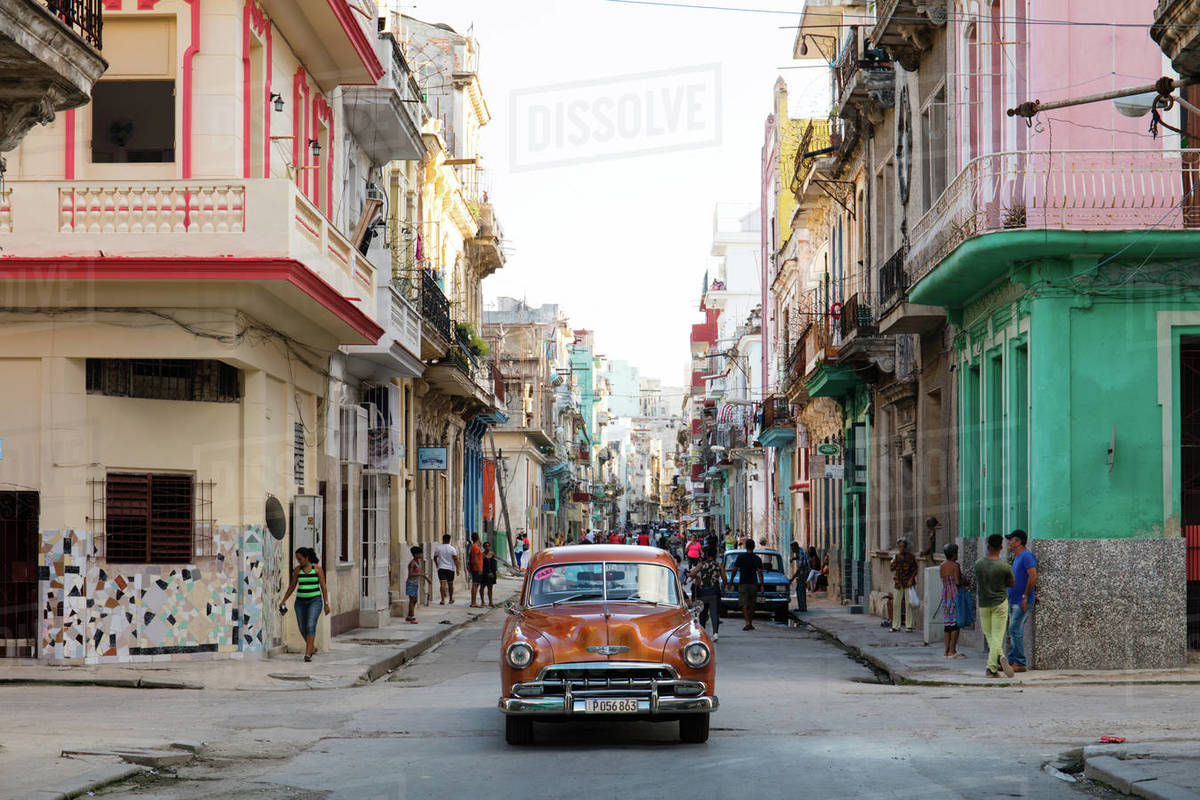 Red vintage car drives along old colourful street in Havana, Cuba, West Indies, Caribbean, Central America Royalty-free stock photo