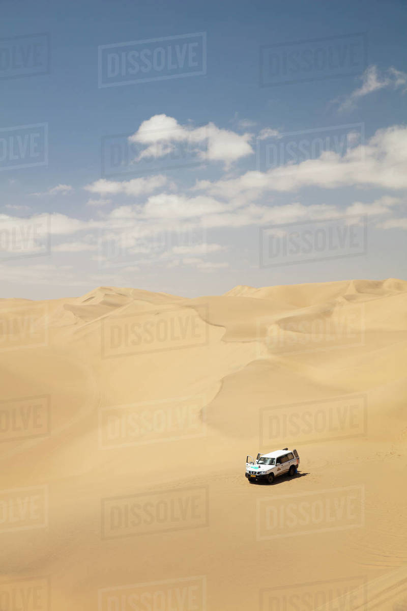 A car pictured within the Sandwich Harbour dunes, Skeleton Coast at midday, Namibia, Africa Royalty-free stock photo