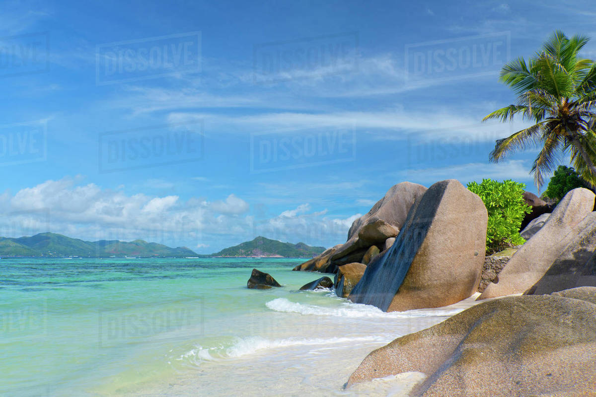 Waves swirling around large granite boulders and palm trees on Anse Source d'Argent, La Digue, Seychelles, Indian Ocean, Africa Royalty-free stock photo