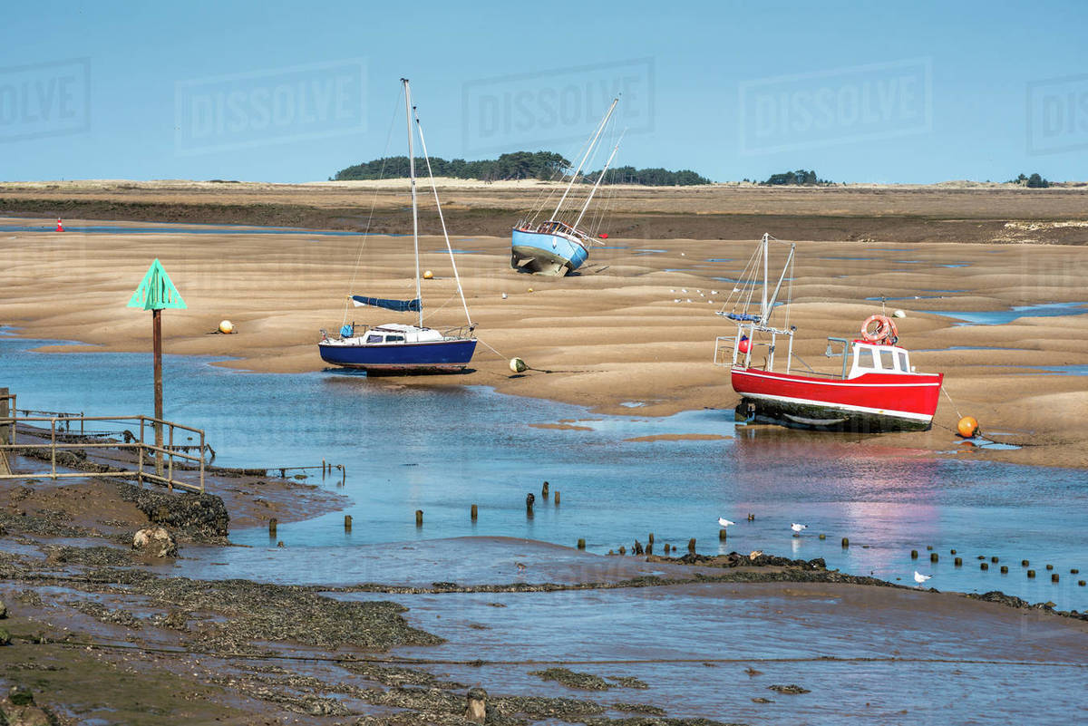 Colourful boats on sandbanks low tide, East Fleet river estuary, Wells next the sea, North Norfolk coast, Norfolk, East Anglia, England, United Kingdom, Europe Royalty-free stock photo