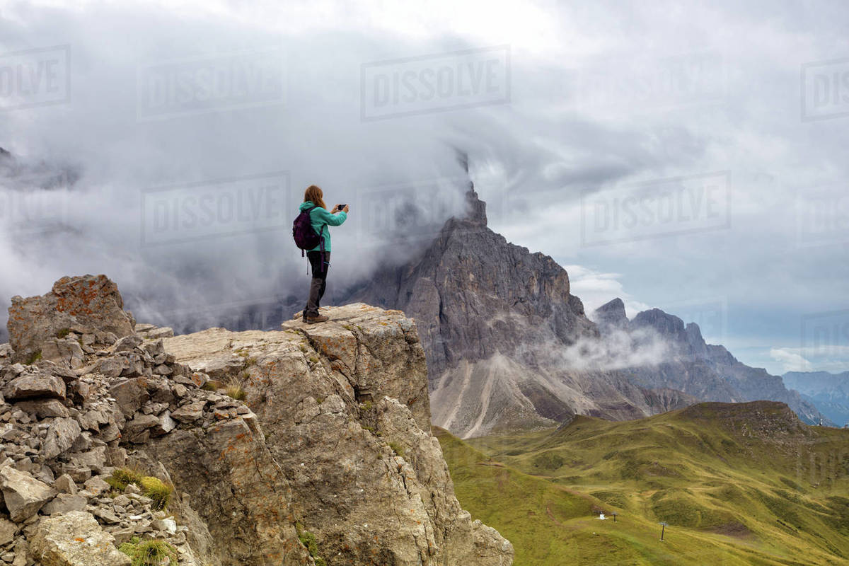 Girl standing at the edge of rock and taking a photo on a smartphone. Dolomites, Italy. Royalty-free stock photo