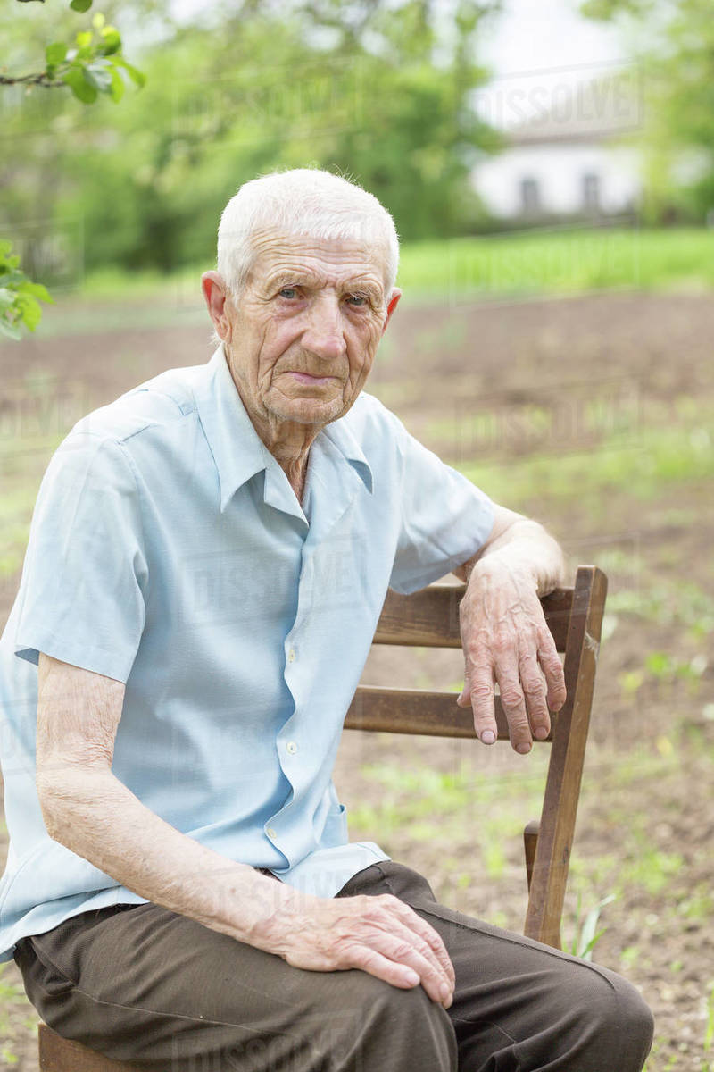 Portrait of  senior man sitting near his house in the village Royalty-free stock photo