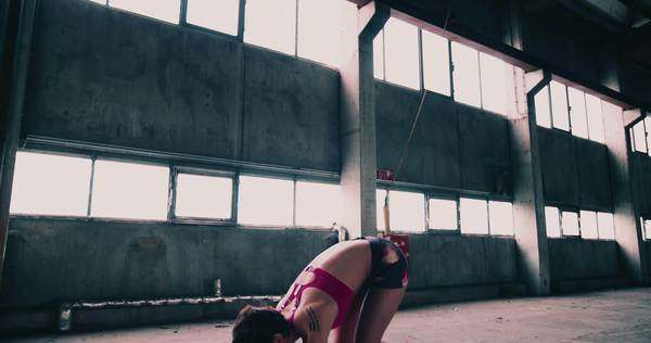 Fit woman in pink colorful sportswear doing burpees on a purple exercise mat in a grungy industrial type space Royalty-free stock video