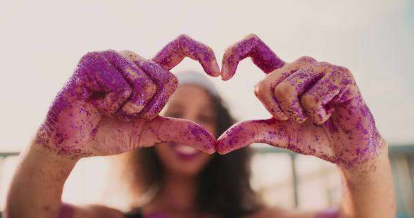 Close-up of a girl's hands covered in pink glitter shaped like a heart with bright sun flare shining through Royalty-free stock video
