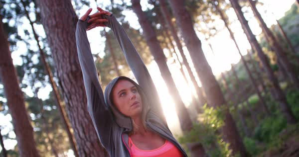 Young woman athlete raising her arms above her head and stretching with her eyes closed enjoying the tranquility of an early morning in the forest Royalty-free stock video