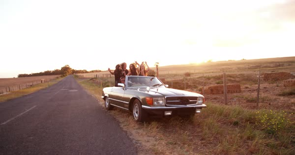 Group of teenager friends dressed in hipster style partying in a country road by cheering with raised arms and embracing with afternoon summer sun flare Royalty-free stock video