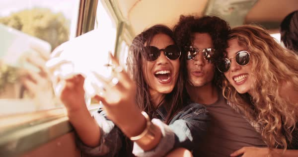 Road trip friends in a car. Man and woman and woman taking a selfie in back of a retro van Royalty-free stock video