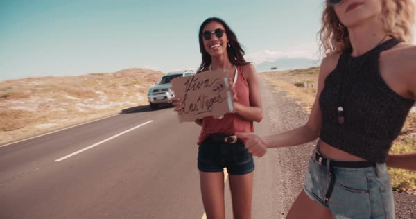 Two friends on a road trip; Blonde hipster woman and boho woman hitchhiking on roadside of highway with thumb out and holding cardboard sign viva Las Vegas Royalty-free stock video