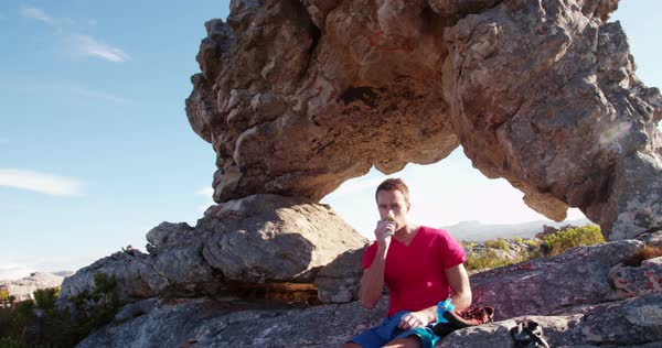 Man opens protein bar while sitting on rock. In the background are extreme rock formations where he has been rock climbing. Royalty-free stock video