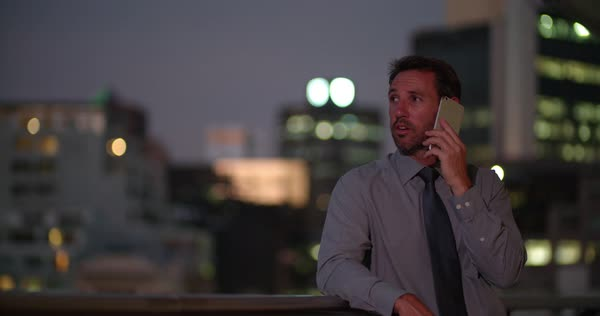 Handsome looking mature businessman talking on the smart phone on his office balcony at night, city lights in background. Royalty-free stock video