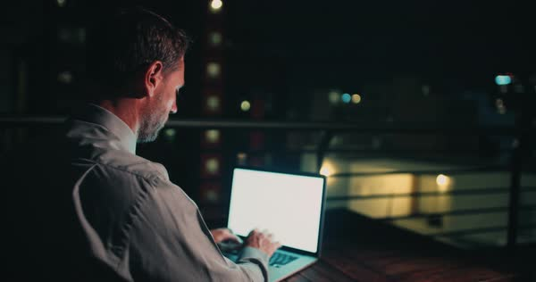 Mature business man working on laptop and sitting on office balcony, trying to stay awake late at night. Cityscape in background Royalty-free stock video