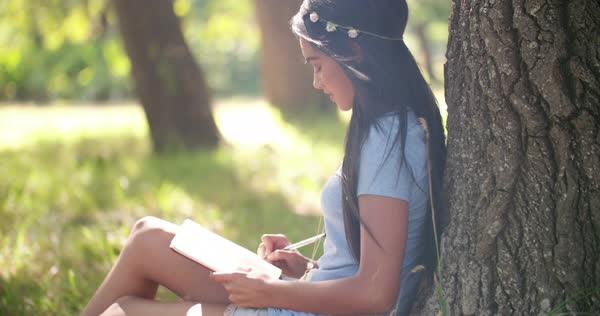 A teenager sits outside in summer and with a flower chain in her hair, smiling and writing in her journal Royalty-free stock video