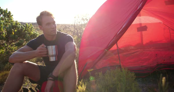 Adventurous young man drinking cup of coffee in the morning next to his tent while camping in the wilderness. He is sitting on his backpack and is ready for hiking in nature Royalty-free stock video