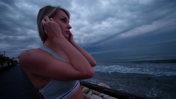 Young fit woman in sportswear putting on headphones to listen to music on a seaside jetty. Royalty-free stock video