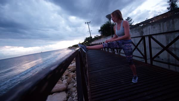 Young woman taking a break from jogging to stretch her legs while listening to a podcast. Royalty-free stock video