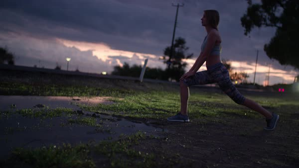 Back lit shot of woman stretching late in the afternoon next to a highway. Royalty-free stock video