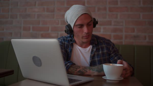 Young handsome hipster listening to a podcast and drinking coffee in modern city coffee shop Royalty-free stock video