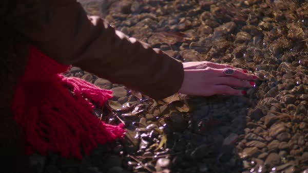 Close up of woman's hand touching the water and stones in river Royalty-free stock video