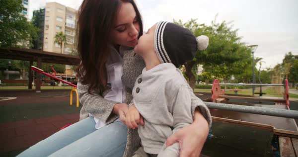 Happy mother giving a kiss to her young boy at the playground Royalty-free stock video