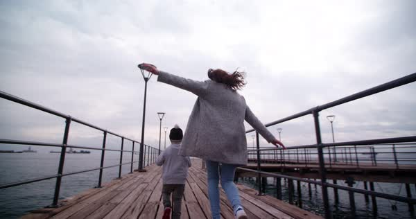 Little boy running and playing aeroplanes with his mother on a pier Royalty-free stock video