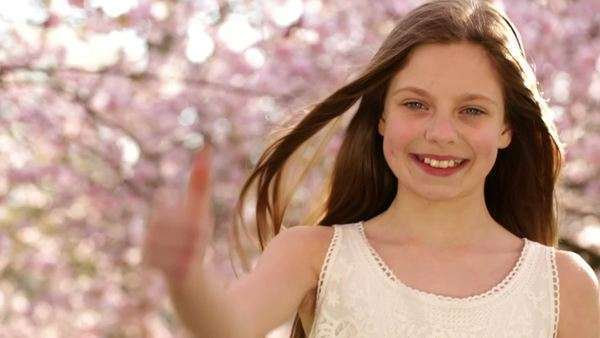 Happy girl giving thumbs up at camera during spring time under cherry blossom trees Royalty-free stock video