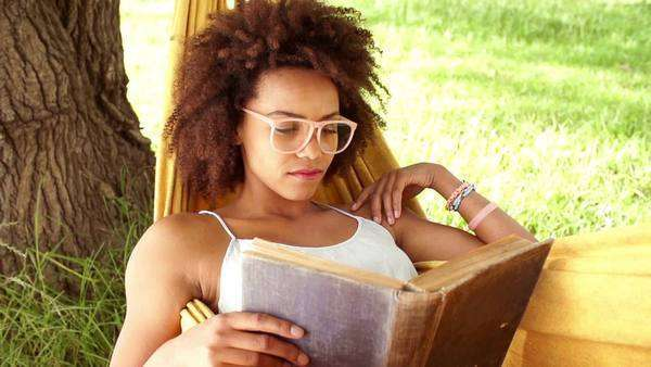 Young African American woman reading book in a hammock at park Royalty-free stock video