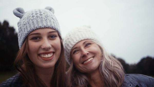 Mother and daughter smile towards the camera whilst wearing matching beanies, kiss on the cheek Royalty-free stock video