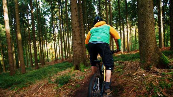 Mountain Biker going downhill in slow motion with mountain bike in the woods, camera following him through trees Royalty-free stock video