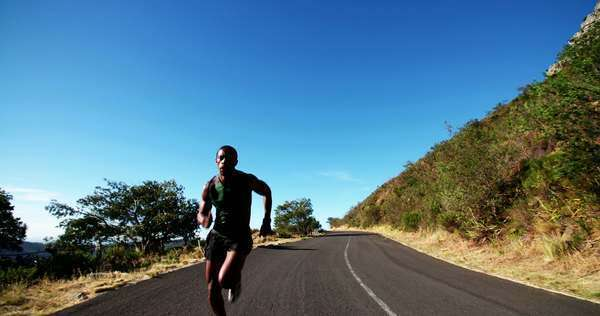 slow motion shot of athlete sprinting along road outdoors on a bright morning in his fitness training Royalty-free stock video