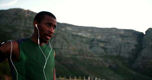 Runner listening to his earphones for some motivation for his training session Royalty-free stock video