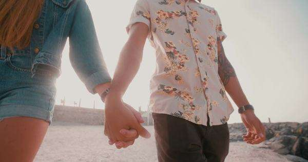 Cropped slow motion shot of a hipster couple walking and holding hands at the beach together Royalty-free stock video