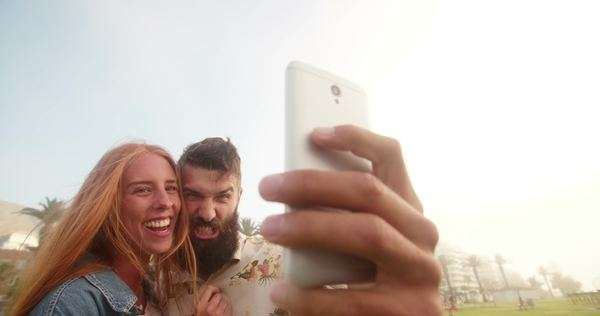 Hipster guy pulling funny face while taking a selfie with his laughing girlfriend outdoors Royalty-free stock video