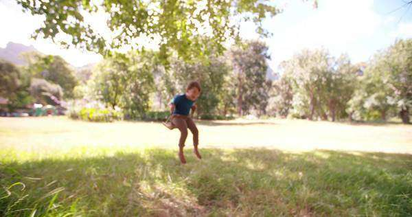 Little boy delightedly swinging in sunny park surrounded by nature Royalty-free stock video
