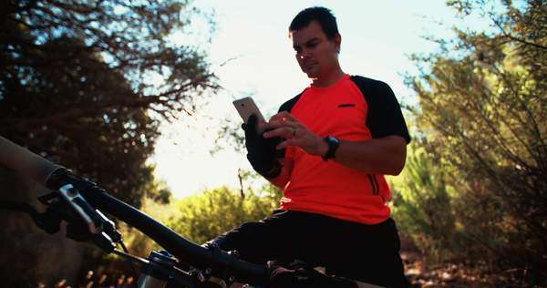 Mountain biker outdoors looking at his smart phone while sitting on his bike Royalty-free stock video