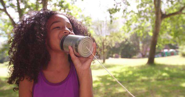 Happy girl talking into a home-made tin can phone outdoors in slow motion Royalty-free stock video