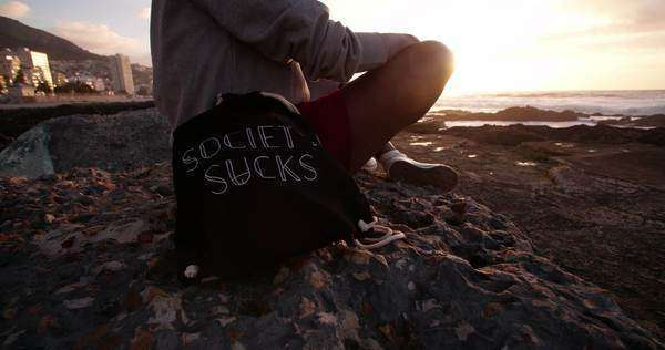 "Cropped shot of an hipster teen sitting on a rock with a bag saying ""society sucks"" Royalty-free stock video"