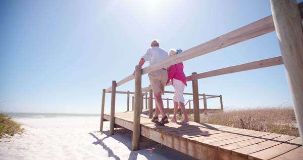 Retired senior adult couple at the beach walking and holding hands in slow motion Royalty-free stock video