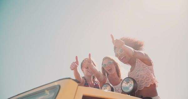 Girl and friends standing in their vacation vehicle posing happily a thumbs up while on a summer road trip Royalty-free stock video