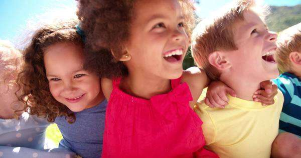 Happy mixed racial group of friendly children sitting in the sun laughing together, panning in slow motion Royalty-free stock video