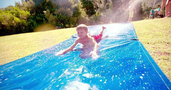 Smiling little boy having fun sliding down a water slide outdoors in the sun in slow motion Royalty-free stock video
