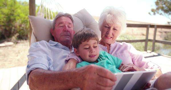 Loving grandparents and their little grandson using a digital tablet together  in slow motion Royalty-free stock video