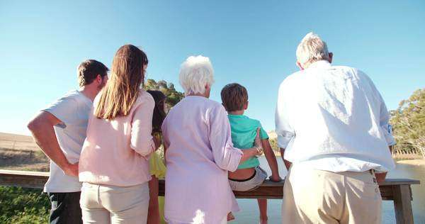Rearview shot of a three generation family standing together on a wooden jetty Royalty-free stock video