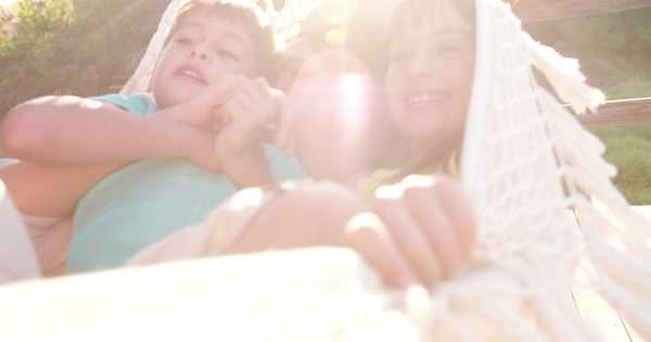 Mom and children sharing a hammock laughing together on a wooden porch with sun flare in slow motion Royalty-free stock video